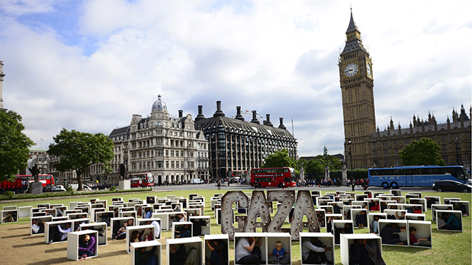 Volunteers sit in wooden boxes at Parliament Square, to represent living conditions in Gaza, during a protest in London August 14, 2014. (Reuters / Dylan Martinez)