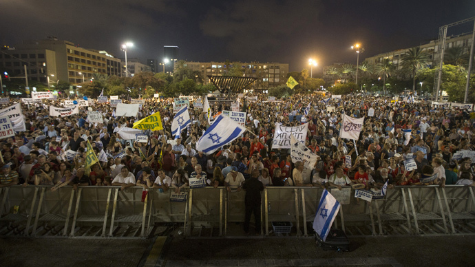 People hold signs during a rally in Tel Aviv's Rabin Square, to show solidarity with residents of Israel's southern communities, who have been targeted by Palestinian rockets and mortar salvoes, August 14, 2014. (Reuters / Baz Ratner)