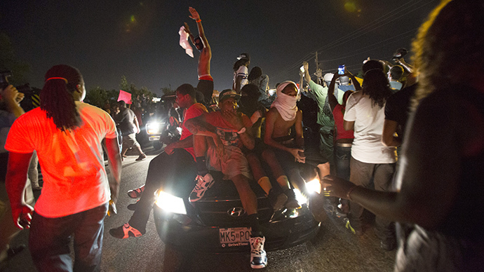 People sit on a car as it drives by a peaceful demonstration, as communities react to the shooting of Michael Brown in Ferguson, Missouri August 14, 2014. (Reuters / Mario Anzuoni)