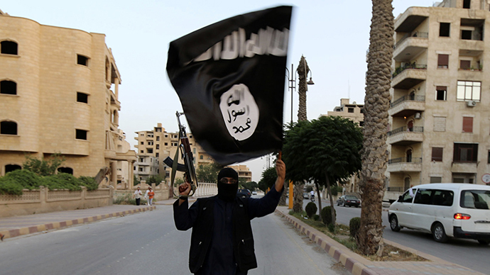 A member loyal to the Islamic State in Iraq and the Levant (ISIL) waves an ISIL flag (Reuters)
