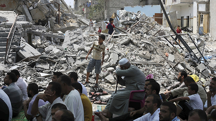 Palestinians attend Friday prayers next to the remains of a mosque which witnesses said was destroyed by an Israel air strike during the Israeli offensive in the central Gaza Strip August 15, 2014. (Reuters / Ibraheem Abu Mustafa)