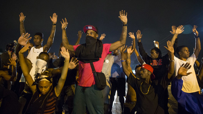 Demonstrators confront police with their arms raised during on-going demonstrations to protest against the shooting of Michael Brown, in Ferguson, Missouri, August 16, 2014. (Reuters/Lucas Jackson)