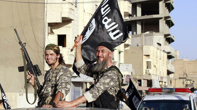 Militant Islamist fighters wave flags as they take part in a military parade along the streets of Syria's northern Raqqa province June 30, 2014. (Reuters)