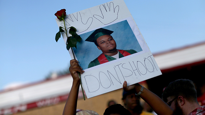 "A demonstrator holds a sign reading, ""Dont Shoot"", with a picture of Michael Brown on August 17, 2014 in Ferguson, Missouri. (AFP Photo / Getty Images / Joe Raedle)"