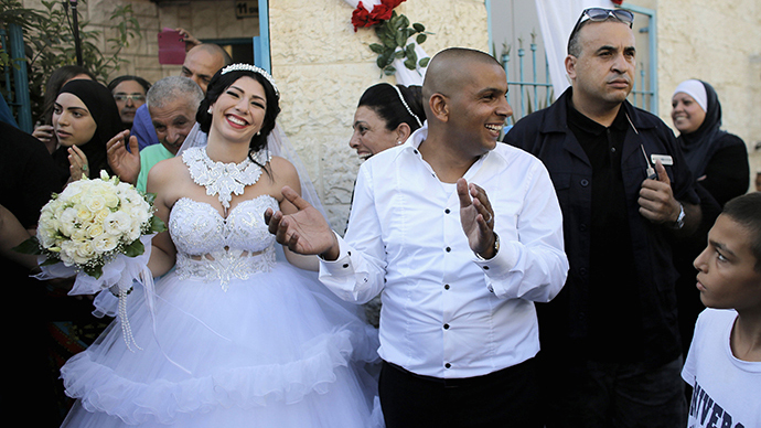Groom Mahmoud Mansour, 26, (C) and his bride Maral Malka, 23, celebrate with friends and family before their wedding in Mahmoud's family house in Jaffa, south of Tel Aviv August 17, 2014. (Reuters / Ammar Awad)