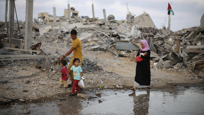 Palestinians walk next to the ruins of houses, which witnesses said were destroyed during the Israeli offensive, on the fifth day of ceasefire in Khan Younis in the southern Gaza Strip August 18, 2014. (Reuters / Ibraheem Abu Mustafa)