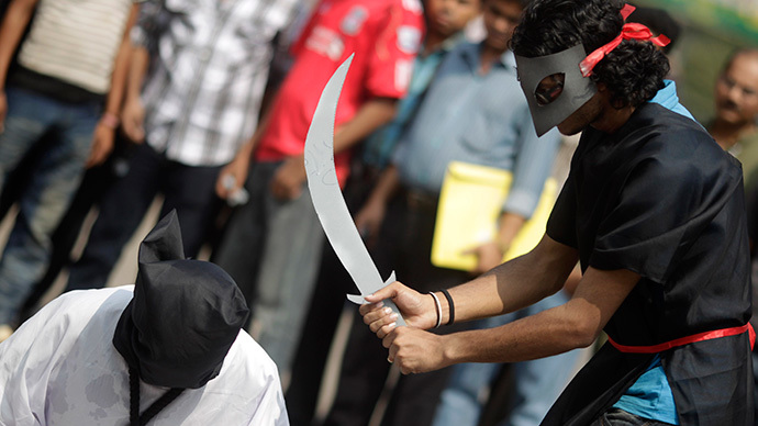 ARCHIVE PHOTO: Members of Magic Movement, a group of young Bangladeshis, stage a mock execution scene in protest of Saudi Arabia beheading of eight Bangladeshi workers in front of National Museum in Dhaka October 15, 2011. (Reuters / Andrew Biraj)