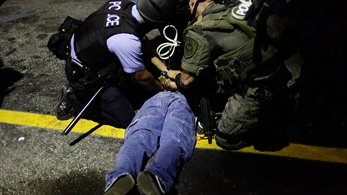 Police in riot gear detain a demonstrator protesting against the shooting of Michael Brown, in Ferguson, Missouri August 19, 2014 (Reuters / Joshua Lott)