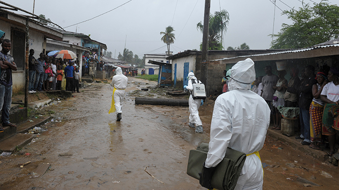 Health workers wearing protective clothing prepare to carry an abandoned dead body presenting with Ebola symptoms at Duwala market in Monrovia August 17, 2014 (Reuters / 2Tango)
