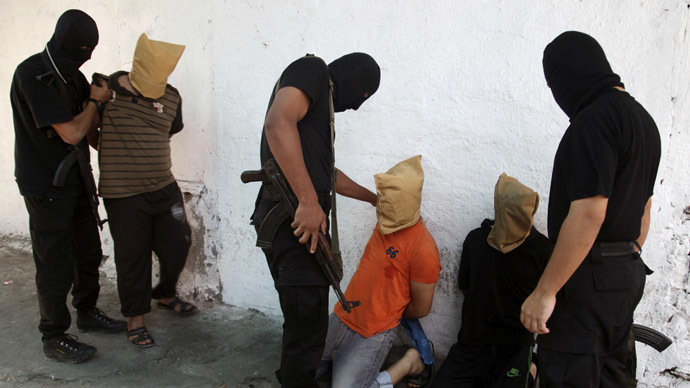 Hamas militants grab Palestinians suspected of collaborating with Israel, before executing them in Gaza City August 22, 2014. (Reuters)