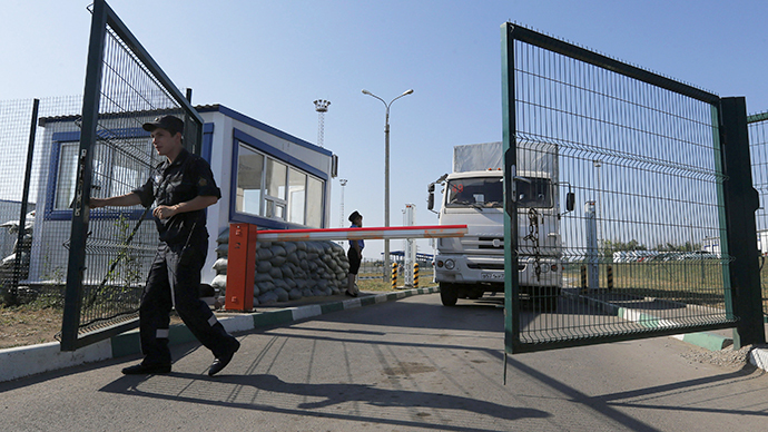 "A Russian border guard opens a gate in front of a truck from a convoy that delivered humanitarian aid for Ukraine on its return to Russia at border crossing point ""Donetsk"" in Russia's Rostov Region August 23, 2014. (Reuters / Alexander Demianchuk)"