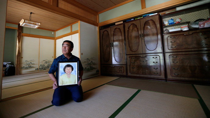 Mikio Watanabe holds a portrait of his late wife Hamako at his home at Yamakiya district in Kawamata town, Fukushima prefecture June 23, 2014.(Reuters / Issei Kato)