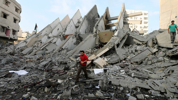 A Palestinian man walks in front of the remains of a tower building housing offices, which witnesses said was destroyed by an Israeli air strike, in Gaza City August 26, 2014.(Reuters / Mohammed Salem)
