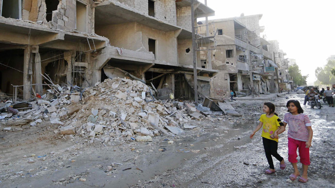 Girls walk past damaged buildings in Aleppo's al-Myassar neighbourhood July 10, 2014. (Reuters/Hosam Katan)
