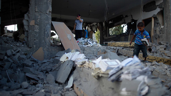 A Palestinian boy collects copies of the Koran from the remains of a mosque, which witnesses said was hit by an Israeli air strike, in Beit Hanoun in the northern Gaza Strip August 25, 2014. (Reuters / Mohammed Salem)