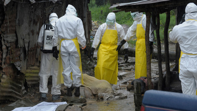 Health workers wearing protective clothing prepare to carry an abandoned dead body presenting with Ebola symptoms at Duwala market in Monrovia August 17, 2014.(Reuters / 2Tango)