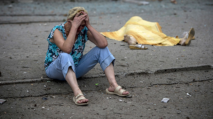 A woman and the body of a person killed in an artillery attack on Lugansk. (RIA Novosti / Valeriy Melnikov)