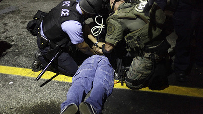 Police in riot gear detain a demonstrator protesting against the shooting of Michael Brown, in Ferguson, Missouri August 19, 2014. (Reuters / Joshua Lott)