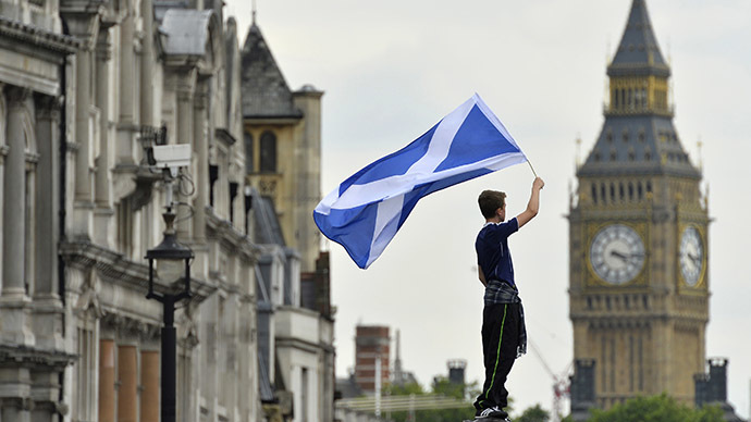 A Scotland soccer fan waves a Scottish saltire flag with Big Ben seen behind in Trafalgar Square in central London, August 14, 2013. (Reuters / Toby Melville)
