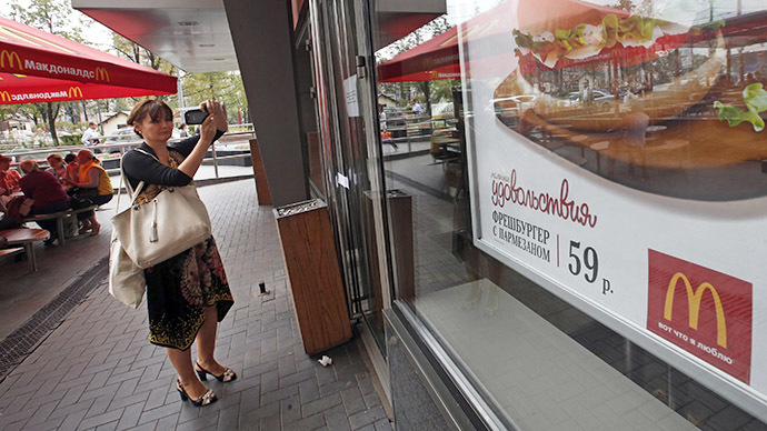 A woman takes pictures of an announcement on the door of a closed McDonald's restaurant (Reuters / Maxim Zmeyev)