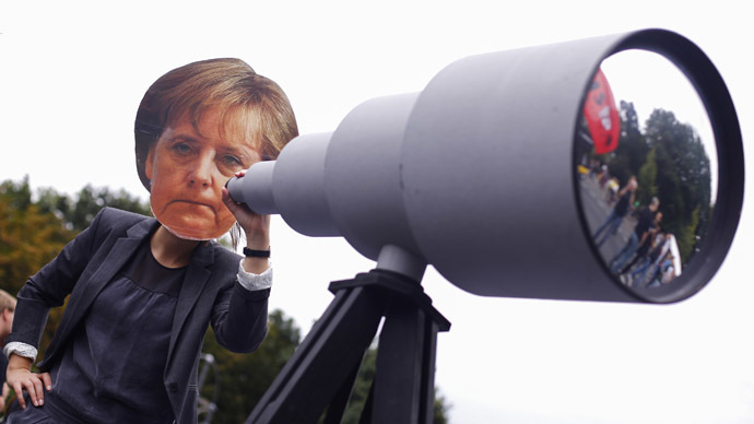 "A woman wearing a mask depicting German Chancellor Angela Merkel stands behind a mock telescope during a ""Freiheit Statt Angst"" (Freedom instead of Fear) protest calling for the protection of digital data privacy and the reigning in of digital surveillance practices, in Berlin August 30, 2014. (Reuters/Thomas Peter )"