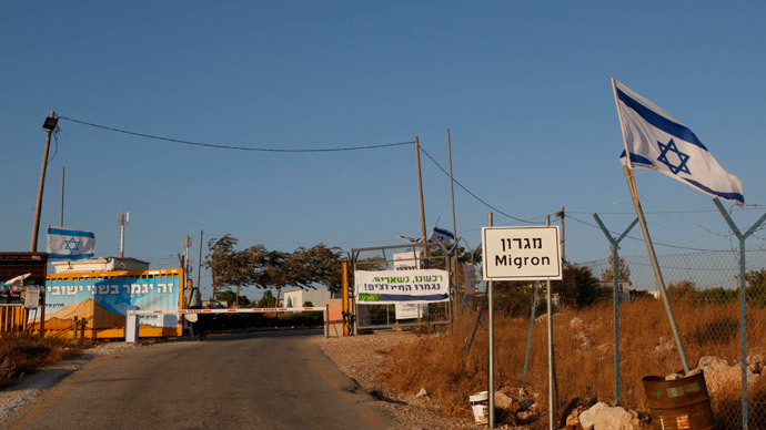 An Israeli soldier stands at the gate of the West Bank settlement of Migron.(AFP Photo / Gali Tibbon )