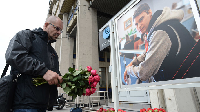 Colleague lays flowers in memory of photo journalist Andrei Stenin killed in southeastern Ukraine, at the Rossiya Segodnya building. (RIA Novosti/Ramil Sitdikov)