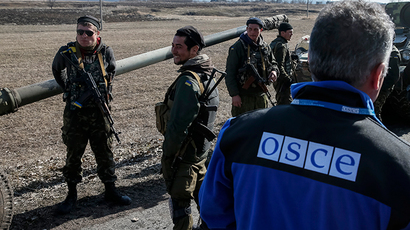 A member of Special Monitoring Mission of the Organization for Security and Cooperation (OSCE) to Ukraine walks along a convoy of Ukrainian armed forces in Blagodatne, eastern Ukraine (Reuters / Gleb Garanich)