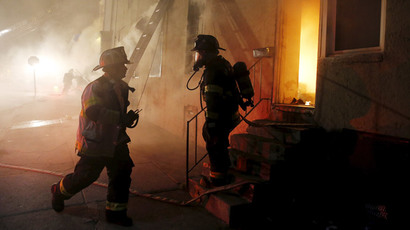 Baltimore firefighters confer as they attack a fire set by rioters in a convenience store and residence at East Biddle Street and Montford Avenue during rioting in Baltimore, Maryland in the early morning hours of April 28, 2015. (Reuters / Jim Bourg)
