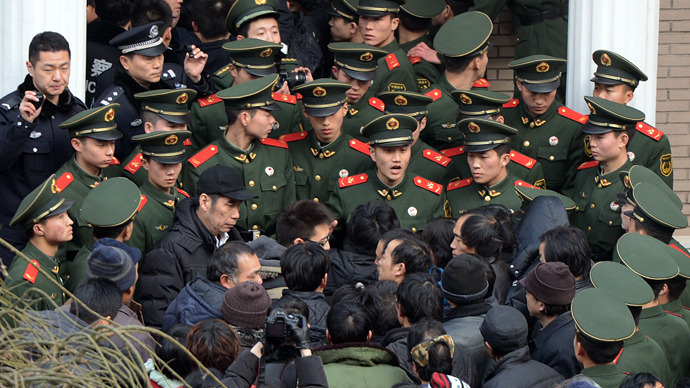 Chinese paramilitary police block access to the residence of a construction firm boss after a group of up to 50 migrant workers stormed past security at the Qijiayuan Diplomatic Compound to protest against what they claim is an unpaid new year bonus in Beijing (AFP Photo / Mark Ralston)