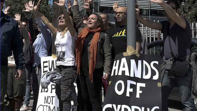 Demonstrators raise their arms in protest as Cypriot President Nicos Anastasiades's convoy drives to the parliament in Nicosia March 18, 2013. (Reuters/Yorgos Karahalis)