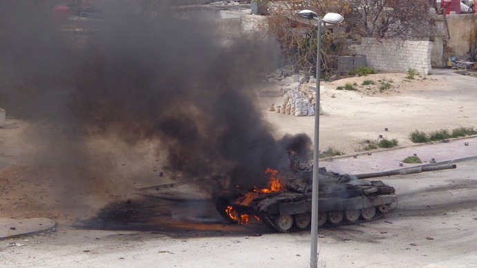 A tank belonging to forces loyal to Syria's President Bashar al-Assad is set on fire during what activists said were clashes between government forces and the Free Syrian Army, in the main south highway near Damascus, March 19, 2013 (Reuters / Mohammed Dimashkia)