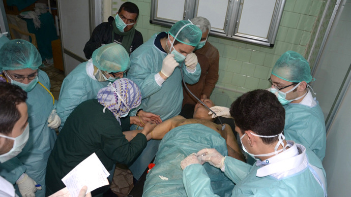 : In this image made available by the Syrian News Agency (SANA) on March 19, 2013, medics and other masked people attend to a man at a hospital in Khan al-Assal in the northern Aleppo province, as Syria's government accused rebel forces of using chemical weapons for the first time (AFP Photo / SANA)