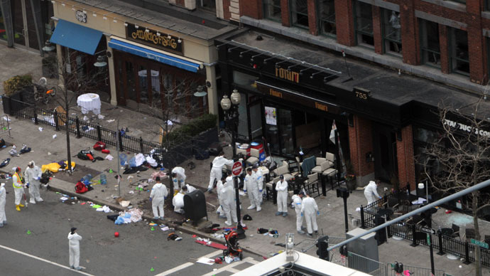 Investigators in white jumpsuits work the crime scene on Boylston Street following yesterday's bomb attack at the Boston Marathon April 16, 2013 in Boston.(AFP Photo / Darren McCollester)