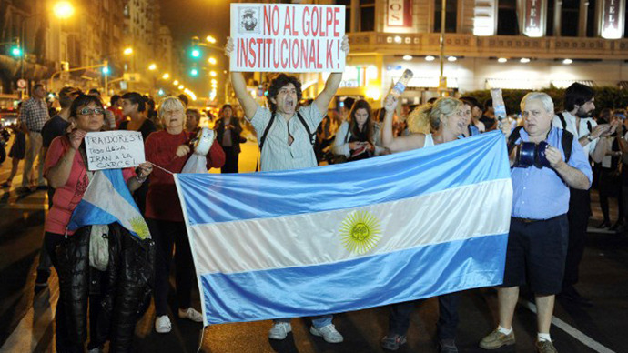 "Argentinians protest with a sign reading ""No to the institutional K coup!"" and a national flag near the Congress building in Buenos Aires on April 25, 2013. (AFP Photo / Alejandro Moritz)"