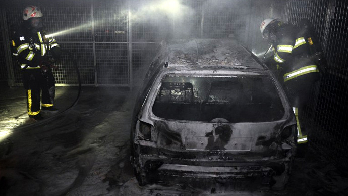 Firemen extinguish a burning car parked in an indoor garage in the Stockholm suburb of Tureberg after youths rioted in several different suburbs for a fourth consecutive night on May 24, 2013. (AFP Photo / Jonathan Nackstrand)