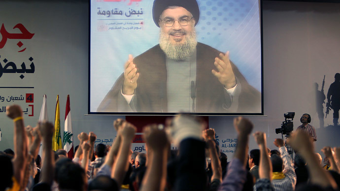 Supporters of Hassan Nasrallah (portrait), the head of Lebanon's militant Shiite Muslim movement Hezbollah raise their fists as they watch him giving a televised address in Beirut (AFP Photo)