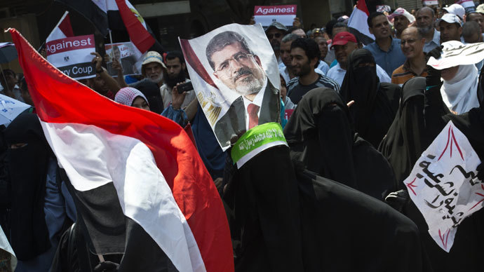 Supporters of the Muslim Brotherhood and ousted Egyptian president Mohamed Morsi hold his picture as they march towards Cairo University to demand his reinstatement in Cairo on July 19, 2013.(AFP Photo / Khaled Desouki)