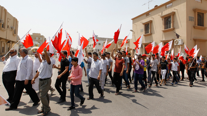 Anti-government protesters holding Bahraini flags march along the streets of the village of Saar during an anti-government protest, west of Manama, August 14, 2013 (Reuters / Hamad I Mohammed)