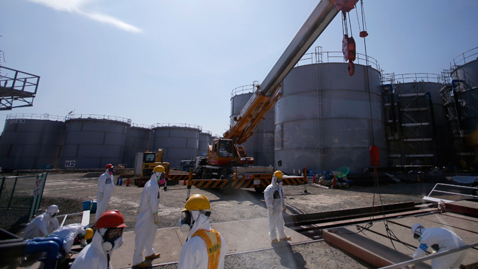 Workers wearing protective suits and masks are seen near tanks of radiation contaminated water at Tokyo Electric Power Company's (TEPCO) tsunami-crippled Fukushima Daiichi nuclear power plant (Reuters / Issei Kato)