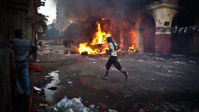 A supporter of the Muslim Brotherhood and of ousted president Mohamed Morsi runs past a burning vehicle during clashes with security officers close to Cairo's Ramses Square, on August 16, 2013 (AFP Photo / Virginie Nguyen Hoang)
