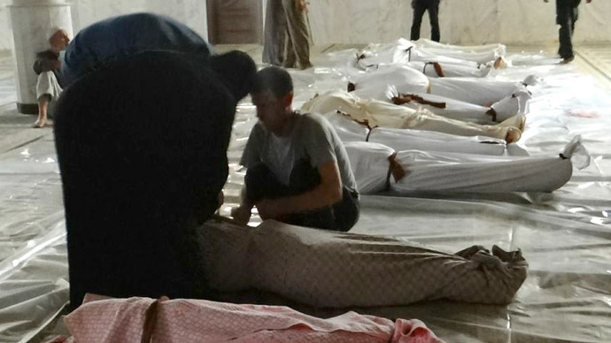 A handout image released by the Syrian opposition's Shaam News Network shows Syrians mourning in front of bodies wrapped in shrouds ahead of funerals following what Syrian rebels claim to be a toxic gas attack by pro-government forces in eastern Ghouta, on the outskirts of Damascus on August 21, 2013.  (AFP Photo/Shaam News Network)