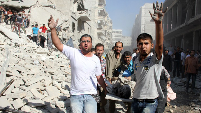 Syrian men evacuate a victim following an air strike by regime forces in the northern city of Aleppo on August 26, 2013. (AFP Photo / Abo Al-Nur Sadk)