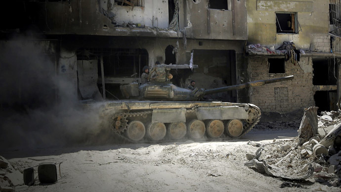 Soldiers of the Syrian government forces patrol on a tank in a devastated street on July 31, 2013 in the district of al-Khalidiyah in the central Syrian city of Homs (AFP Photo)