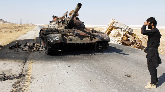 A Free Syrian Army fighter stands near a damaged military tank that belonged to the forces loyal to Syria's President Bashar Al-Assad after they seized it, in Aleppo's town of Khanasir August 29, 2013. (Reuters/Molhem Barakat)