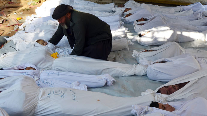 A man holds the body of a dead child among bodies of people activists say were killed by nerve gas in the Ghouta region, in the Duma neighbourhood of Damascus August 21, 2013.(Reuters / Bassam Khabieh)