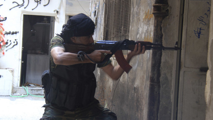 A Syrian fighter aims his weapon as he takes a defensive position in the refugee camp of Yarmouk, near Damascus September 11, 2013.  (Reuters/Ward Al-Keswani)