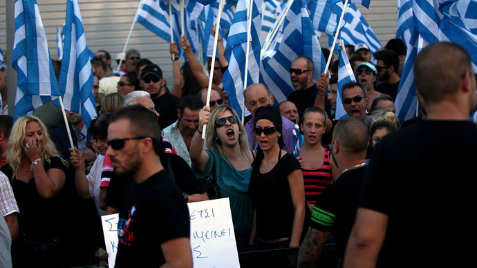 Supporters of the extreme far-right Golden Dawn party shout slogans while holding Greek flags during a protest in solidarity with the party's arrested lawmakers outside the police headquarters in Athens on September 28, 2013.(AFP Photo / Angelos Tzortzinis)