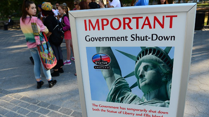 Tourists walk by a sign announcing that the Statue of Liberty is closed due to a US government shutdown in New York, October 1, 2013. (AFP Photo / Emmanuel Dunand)
