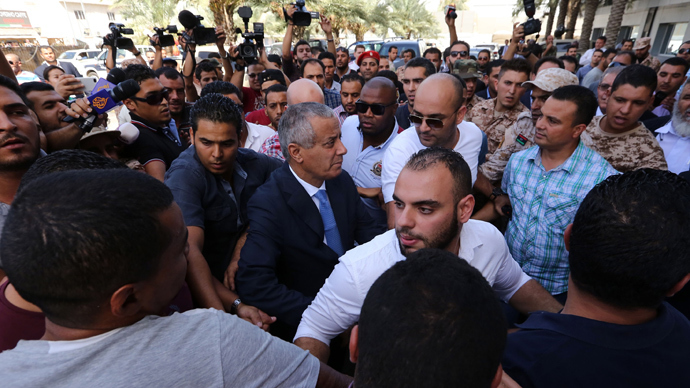 Libyan Prime Minister Ali Zeidan (C) arrives at the government headquarters in Tripoli on October 10, 2013 (AFP Photo / Mahmud Turkia)
